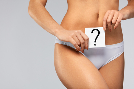 genital: Feminine Health. ?loseup Of Young Woman Fit Body In White Bikini Panties Holding White Card With Question On It Near Her Belly. Beautiful Female Body In Underwear. Gynecology Concept. High Resolution