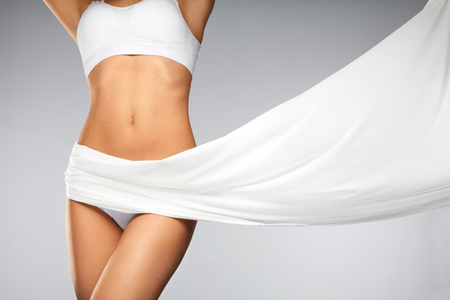 Women Health. Beautiful Healthy Woman With Fit Slim Body, Silky Smooth Soft Skin In White Bikini Underwear. Closeup Of Textile Flying On Perfect Female Body Shape. Body Care Concept. High Resolution Banque d'images
