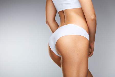 Cuerpo delgado de la mujer hermosa. ? Loseup De saludable Chica con cuerpo en forma, piel suave, las caderas y las nalgas apretadas firmemente en la ropa interior de bikini. Perfecto cuerpo femenino en forma con la parte posterior atractiva y Big Butt. Alta resolución