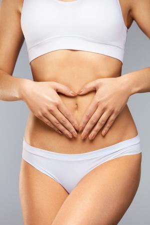 Frauen Gesundheit. ? Loseup Schöne gesunde junge Frau mit sexy Fit schlanken Körper, glatte, weiche Haut in der weißen Unterwäsche Hände halten In Herzform am Bauch. Körperpflege, Verdauung Konzept. Hohe Auflösung Standard-Bild - 74374586