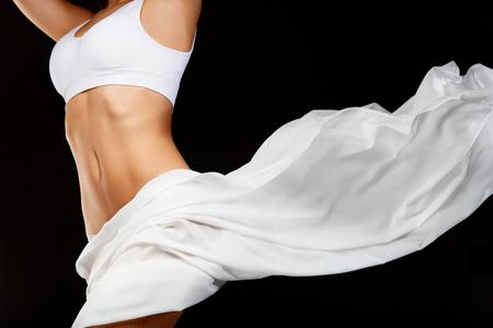 Lichaamsverzorging. Mooi gezond wijfje met perfecte geschikte slanke lichaamsvorm, zijdeachtige vlotte zachte huid in wit Bikiniondergoed en vliegende textiel op zwarte achtergrond. Gezondheid Concept. Hoge resolutie Stockfoto