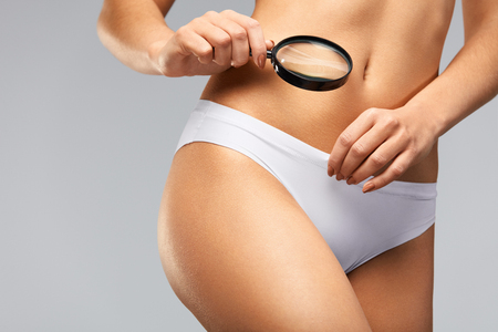 sexual anatomy: Female Health. ?loseup Of Young Woman With Slim Body Looking Through Magnifying Glass Into White Bikini Panties. Beautiful Girl In Underwear Holding Magnifier In Hand, Exploring Body. High Resolution