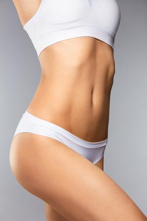 cuerpo femenino: Cuidado del cuerpo. Hermosa mujer en forma con el cuerpo delgado apto, saludable suave piel suave en bikini blanco bragas sobre fondo gris. Primer Cuerpo Femenino En Ropa Interior. Conceptos De Salud Y Dieta. Alta resolución Foto de archivo