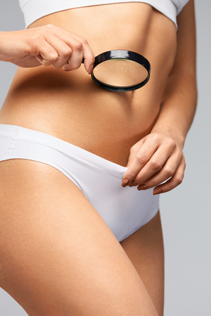 Female Health. ?loseup Of Young Woman With Slim Body Looking Through Magnifying Glass Into White Bikini Panties. Beautiful Girl In Underwear Holding Magnifier In Hand, Exploring Body. High Resolution