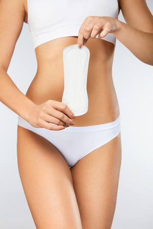 Female Hygiene. ?loseup Of Beautiful Woman With Fit Slim Body In White Underwear Holding Sanitary Towel, Panty Liner In Hands. Girl Holding Clean Period Pad, Feminine Intimate Product. High Resolution Stock Photo