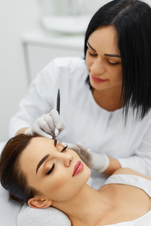 Make-Up. Beautiful Young Woman Receiving Permanent Brow Makeup In Beauty Salon. Closeup Of Beautician Doing Eyebrow Tattoo For Female Face. Cosmetology Treatment. High Resolution Stock Photo
