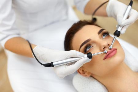 Pelle facciale. Primo piano di bella donna che riceve trattamento viso microcorrente da terapeuta al salone Spa. Beautician che utilizza impulsi elettrici per le procedure facciali. Cosmetologia. Alta risoluzione Archivio Fotografico - 75161688