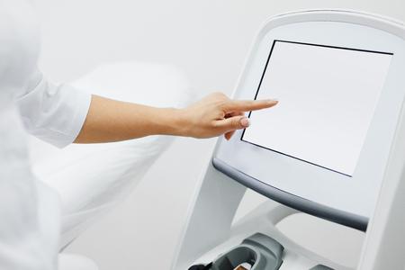 Hautbehandlung Ausrüstung. Medizinischer Arbeiter setzt Indizes auf Bildschirm der Laser-Licht-Haar-Abbau-Vorrichtung. Nahaufnahme des Kosmetikers, der Schönheits-Maschine in der Kosmetik-Mitte, Schönheits-Salon verwendet. Hohe Auflösung Standard-Bild - 74892825