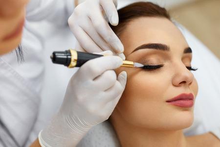 美容女性の顔。美容師から永久化粧を受け取る美しい女の子。スパ ・ サロンで若い女性取得眼瞼タトゥーのクローズ アップ。メイクや化粧品。美