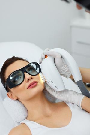 光源。美しい女性のサロンで肌の若返り、皮膚剥離を受信のクローズ アップ。美容師は顔の皮膚の舗装を行います。美容。高分解能