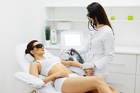 Woman Beauty. Beautician Doing Epilation On Beautiful Girl's Body In Medical Center. Female Receiving Laser Light Hair Removal Treatment For Hairless Smooth Skin At Cosmetology Salon. High Resolution