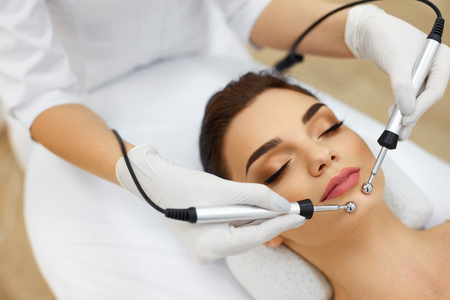 Facial Skin. Closeup Of Beautiful Woman Receiving Facial Microcurrent Treatment From Therapist At Spa Salon. Beautician Using Electrical Impulses For Facial Procedures. Cosmetology. High Resolution Stock Photo