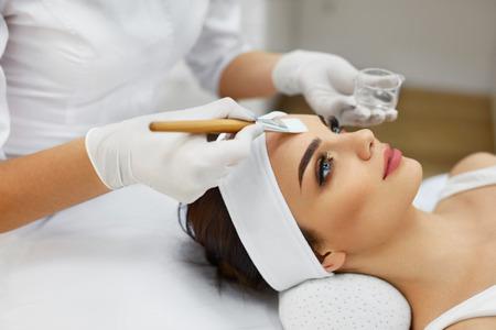 Cuidado de la piel de la cara. Esteticista aplicar máscara de aceite de belleza en cara que usa el cepillo en salón del balneario. Primer Del Cliente femenino consiguen procedimiento Hidratante En la clínica de belleza. Cosmetología. Alta resolución