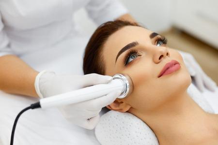 Cosmetología. Hermosa mujer recibiendo cavitación de ultrasonido de piel facial. Primer plano de rostro femenino que recibe cosméticos antienvejecimiento con máquina de cavitación por ultrasonido. Cuidado del cuerpo. Alta resolución