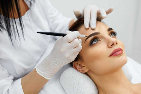 Maquillaje permanente para las cejas. Primer De La Mujer Hermosa Con La Nave Espesa En El Salón De Belleza. Esteticista haciendo tatuaje de la ceja para la cara femenina. Procedimiento de Belleza. Alta resolución