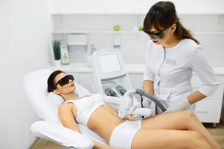 Cosmetology. Young Woman With Beautiful Body At Spa Salon Receiving Laser Hair Removal Procedure. Beautician Using Modern Apparatus For Spa Procedures. Skin And Beauty Care. High Resolution