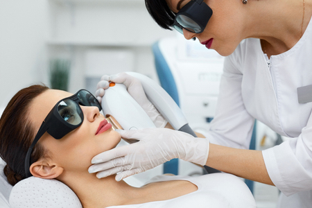resurfacing: Photorejuvenation. Closeup Of Beautiful Woman Receiving Skin Rejuvenation And Dermabrasion In Beauty Salon. Beautician Doing Facial Skin Resurfacing. Cosmetology. High Resolution Stock Photo