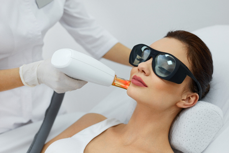 Cosmetic Laser Procedures. Beautician Uses Skin Resurfacing Equipment To Resurface Beautiful Woman Skin. Closeup Of Female Receiving Beauty Treatment, Therapy. Body Care. High Resolution