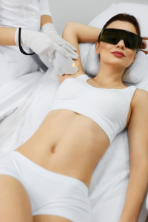 light hair: Laser Hair Removal. Closeup Of Beautician Removing Hair Of Young Womans Armpit. Beauty Epilation Treatment In Cosmetic Beauty Clinic. Hairless Smooth And Soft Skin. Body Care. High Resolution Stock Photo