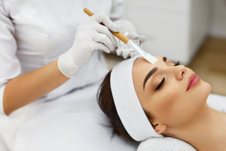 Face Skin Care. Beautician Applying Beauty Oil Mask On Face Using Brush In Spa Salon. Closeup Of Female Client Getting Hydrating Procedure In Beauty Clinic. Cosmetology. High Resolution Archivio Fotografico