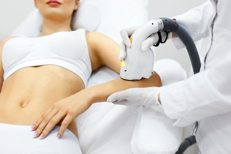 Cosmetology. Closeup Of Beautician Doing Laser Epilation Treatment On Beautiful Female Body, Removing Hair On Silky Skin. Woman Receiving Light Hair Removal Procedure In Beauty Salon. High Resolution Stock Photo