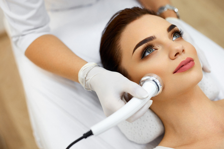 Cosmetology. Beautiful Woman Receiving Facial Skin Ultrasound Cavitation. Closeup Of Female Face Receiving Anti-Aging Cosmetics Using Ultrasound Cavitation Machine. Body Care. High Resolution