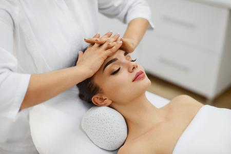 Gesichtshautpflege. Nahaufnahme der schönen weiblichen empfangenden Gesichtsmassage vom Spezialisten in der Badekurort-Mitte. Masseur massiert den Kopf der Frau im Schönheitssalon. Kosmetologieverfahren. Hohe Auflösung Standard-Bild
