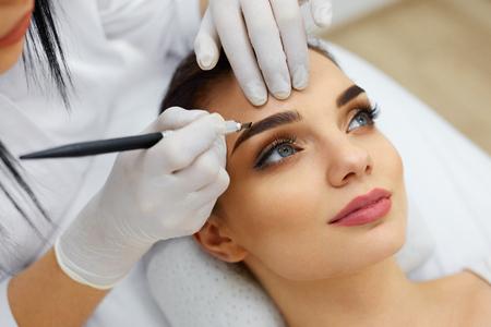 Makijaż. Beautician Ręce Doing Tatuaż Brwi Na Kobiety Face.Permanent Makeup Brow W Salonie Piękności. Closeup Specjalista Robienie Błękitne Tatuaże Dla Kobiet. Leczenie kosmetyczne. Wysoka rozdzielczość