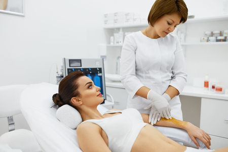 Hot Waxing. Beautiful Young Woman Getting Beauty Procedures For Hair Removal In Beauty Spa Salon. Closeup Of Beautician Applying Hot Wax On Female Client Hand. Skin And Body Care. High Resolution