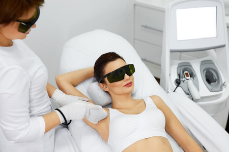 Laser Hair Removal. Closeup Of Beautician Removing Hair Of Young Woman's Armpit. Beauty Epilation Treatment In Cosmetic Beauty Clinic. Hairless Smooth And Soft Skin. Body Care. High Resolution Standard-Bild