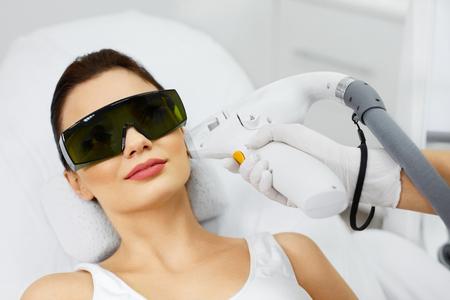 Depilación luz. Primer de la mujer joven en la clínica de spa que reciben tratamiento facial. Mujer atractiva que consigue procedimientos láser para la piel del salón de belleza. Cuidado de la belleza. Alta resolución Foto de archivo