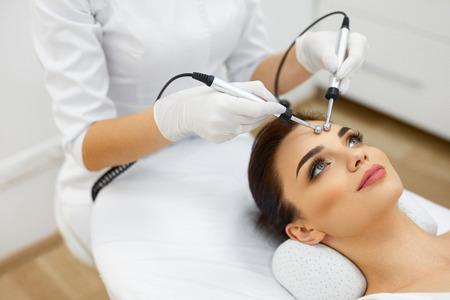 Obličejová kůže. Detailní záběr na krásná žena přijímání obličeje Microcurrent Léčba od terapeuta v lázeňském salonu. Beautician použití elektrických impulsů pro obličejové procedury. Kosmetologie. Vysoké rozlišení Reklamní fotografie