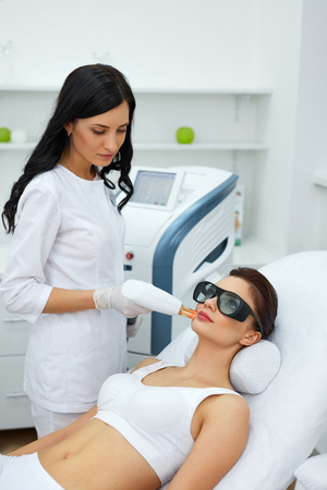 resurfacing: Beauty Procedure. Closeup Of Beautician Using Laser Therapy For Facial Skin Rejuvenation. Beautiful Healthy Woman Face Getting Skin Resurfacing In Spa Salon. Body Treatment. High Resolution