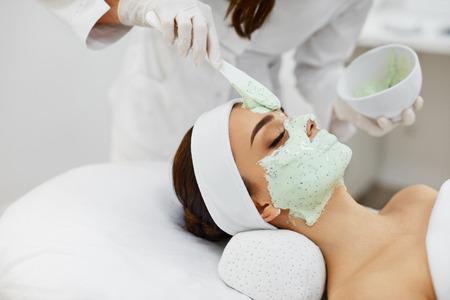 Tratamiento de la piel facial. ? Loseup de la hermosa joven que recibe la máscara cosmética en salón de belleza. Esteticista aplicar máscara de alginato en cara femenina con la piel suave suave. Cosmetología. Alta resolución