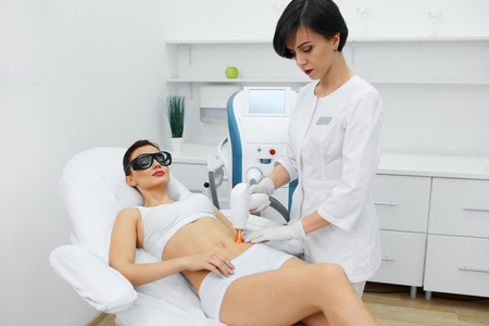 resurfacing: Cosmetic Laser Procedures. Beautician Uses Skin Resurfacing Equipment To Resurface Beautiful Woman Skin. Closeup Of Female  Receiving Beauty Treatment, Therapy. Body Care. High Resolution