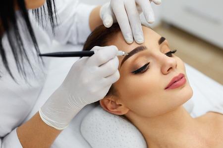 メイク。美容師の手のサロンで女性 Face.Permanent 眉化粧眉タトゥーをしています。女性の刺青眉を行うスペシャ リストのクローズ アップ。美容治療