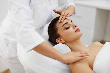 Facial Beauty Treatment. Closeup Of Beautiful Woman Getting Beauty Treatment, Hand Massage At Day Spa Salon. Massauer Massaging Female Face With Aromatherapy Oil. Skin And Body Care. High Resolution Stock Photo