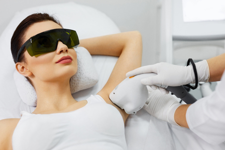 Laser Hair Removal. Closeup Of Beautician Removing Hair Of Young Womans Armpit. Beauty Epilation Treatment In Cosmetic Beauty Clinic. Hairless Smooth And Soft Skin. Body Care. High Resolution Stock Photo