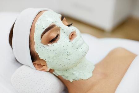 Cuidado de la piel mujer Primer de la muchacha hermosa con la máscara cosmética en piel facial en salón de belleza. Hembra joven con la cara cubierta con la máscara que humedece verde del alginato. Tratamiento de belleza. Alta resolución