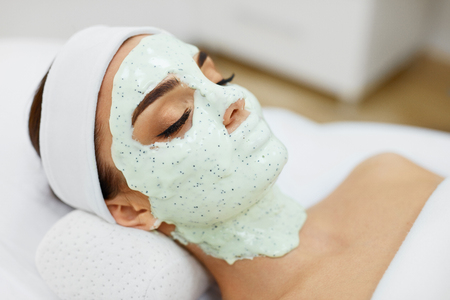Woman Skin Care. Closeup Of Beautiful Girl With Cosmetic Mask On Facial Skin In Beauty Salon. Young Female With Face Covered With Green Moisturizing Alginate Mask. Beauty Treatment. High Resolution Stock Photo