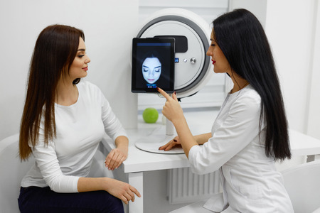 Medical Consultation. Closeup Of Beauty Doctor Giving Information To Woman About Condition Of Her Facial Skin. Beautician And Female Talking In Salon. Face Analysis Treatment. High Resolution