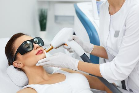美容。スパサロンで若返り治療を受けて美しい若い女性のクローズ アップ。女性のクライアントの皮膚ふじょうと皮膚剥離を行う医療従事者。皮膚