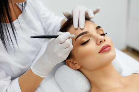 Permanent Makeup For Eyebrows. Closeup Of Beautiful Woman With Thick Brows In Beauty Salon. Beautician Doing Eyebrow Tattooing For Female Face. Beauty Procedure. High Resolution Stock Photo