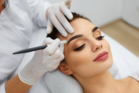 Permanent Makeup For Eyebrows. Closeup Of Beautiful Woman With Thick Brows In Beauty Salon. Beautician Doing Eyebrow Tattooing For Female Face. Beauty Procedure. High Resolution Stockfoto
