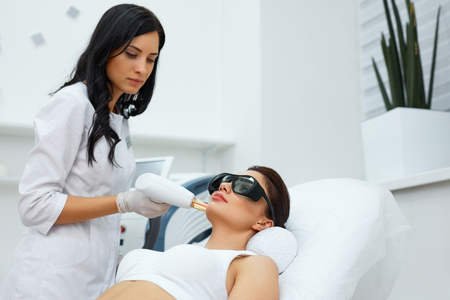 Beauty Procedure. Closeup Of Beautician Using Laser Therapy For Facial Skin Rejuvenation. Beautiful Healthy Woman Face Getting Skin Resurfacing In Spa Salon. Body Treatment. High Resolution