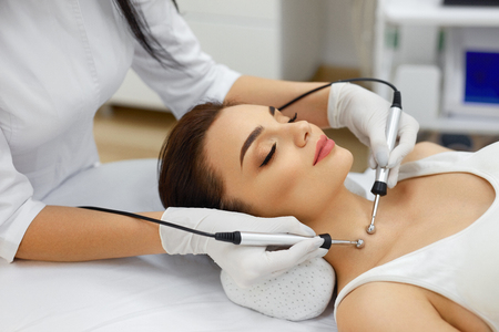 Cosmetology. Beautiful Woman At Spa Clinic Receiving Stimulating Electric Facial Treatment From Therapist. Closeup Of Young Female Face During Microcurrent Therapy. Beauty Treatment. High Resolution