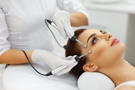얼굴 피부. 스파 살롱에서 치료사에서 얼굴 Microcurrent 치료를 받고하는 아름 다운 여자의 근접 촬영. 얼굴 절차를위한 전기 충격을 사용하는 미용사. 미