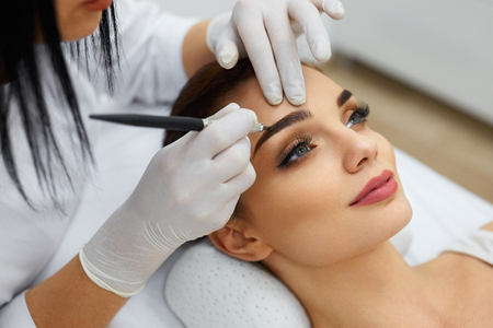 Permanent Makeup For Eyebrows. Closeup Of Beautiful Woman With Thick Brows In Beauty Salon. Beautician Doing Eyebrow Tattooing For Female Face. Beauty Procedure. High Resolution