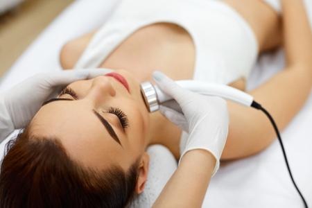 Cosmetología. Mujer hermosa que recibe la piel facial de ultrasonido cavitación. Primer plano de la cara femenina Recepción de cosméticos antienvejecimiento usando ultrasonido Máquina de cavitación. Cuidado del cuerpo. Alta resolución
