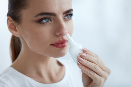 spaying: Healthcare. Closeup Of Beautiful Young Woman Using Nasal Spray Indoors. Portrait Of Sick Girl Having Flu Spaying Medical Nasal Drops For Blocked Running Nose. Illness And Sickness. High Resolution Stock Photo
